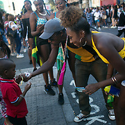 A small boy is shown how to use his whistle cheering on the parade. Hackney carnival 2016 took place on a hot Indian summer's day, September 2016 with the streets full of partying people.