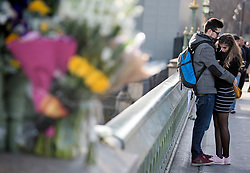© Licensed to London News Pictures. 22/03/2018. London, UK. An emotional young couple embrace each other, next to floral tributes on Westminster Bridge in London on the one year anniversary of the Westminster Bridge Terror attack. Lone terrorist, 52-year-old Briton Khalid Masood, killed four people by driving a car at pedestrians then managed to gain entry to the grounds of the Houses of Parliament, killing police officer Keith Palmer. Photo credit: Ben Cawthra/LNP