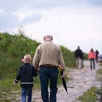 A grandfather walking with his grandson along the shore near Kronborg Castle in Denmark.