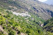 Landscape of the River Rio Poqueira gorge valley, High Alpujarras, Sierra Nevada, Granada Province, Spain whitewashed village of Pampaneria