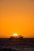 Orange Glowing Sun Setting Behind Silhoette of Fishing Boat Anchored Alone at Sea, Celestun, Yucatan, Gulf of Mexico 2007