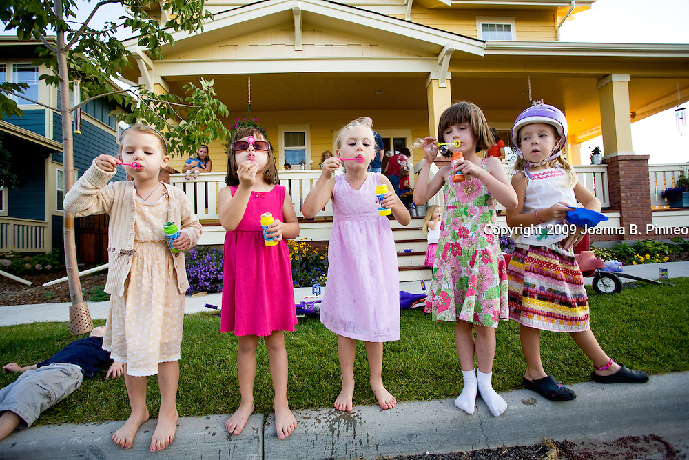Neighborhood girls practice blowing bubbles at a porch party in Bradburn Village, a new urbanist community in Westminster, Colorado. New urbanist communities front porches are important to the sense of home. These communities encourage walking to restaurants and shops, to the park and the homes of your friends and neighbors.