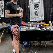 Sam Turner Ink, tattoo a client at The Great British Tattoo Show, on 26 May 2019, London, UK.