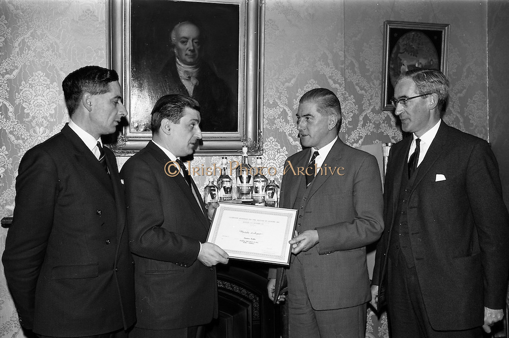 20/02/1964<br /> 02/20/1964<br /> 20 February 1964<br /> Presentation of World Wines and Liquor Olympics award to John Power and Son Ltd at the John's Lane Distillery. The prize was awarded for their Sarotov Vodka which received the Premier Award in its Category in the World Wines and Liquor Olympics. Picture shows M. andre L. de Vogelaere (2nd from right), Counsellor of the Belgian Embassy presenting the award to Mr P.A. Leavy, Sales Manager John Power and Son Ltd. On the left is Mr F.J. O'Reilly, Chairman and Managing Director and on the right, Mr John A. Ryan, Joint Managing Director of John Power and Sons Ltd.