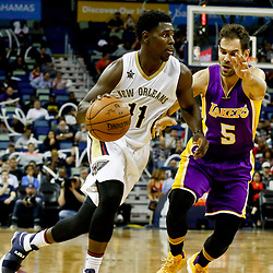 Nov 29, 2016; New Orleans, LA, USA; New Orleans Pelicans guard Jrue Holiday (11) drives past Los Angeles Lakers guard Jose Calderon (5) during the second half of a game at the Smoothie King Center. The Pelicans defeated the Lakers 105-88. Mandatory Credit: Derick E. Hingle-USA TODAY Sports