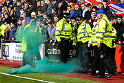 Police officers and security stewards react as a distress flare thrown from the Hibernian end empties green smoke at their feet during the Ladbrokes Scottish Premiership match between Heart of Midlothian and Hibernian at Tynecastle Stadium, Gorgie, Scotland on 31 October 2018.