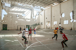 Boys playing football in a bombed out gym in Gaza. From a series of photos commissioned by  British NGO, Medical Aid for Palestinians (MAP).