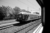 arrivati in stazione la littorina incrocia un treno delle ferrovie di stato. Reportage che analizza le situazioni che si incontrano durante un viaggio lungo le linee ferroviarie delle Ferrovie Sud Est nel Salento