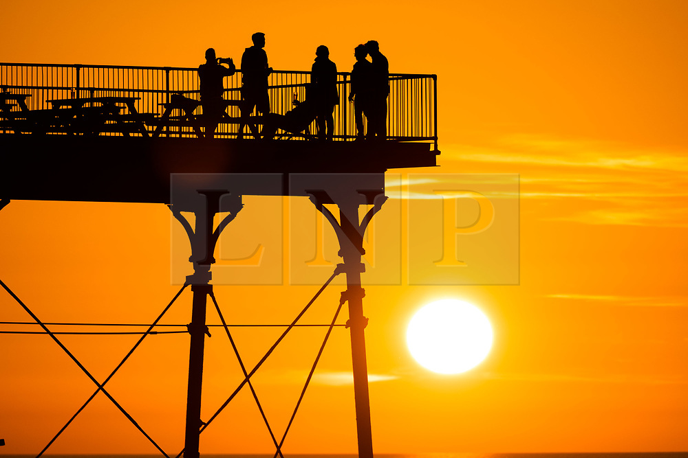 ©Licensed to London News Pictures. 19/09/2019 Aberystwyth UK. <br /> The sun setting gloriously over  Cardigan Bay silhouettes peopke enjoying an al fresco drink on the pier at the end of a day of unbroken clear blue skies and warm September sunshine in Aberystwyth, west Wales.   as the 'indian summer' mini heat-wave continues over much of the souther parts of the UK<br /> Photo credit Keith Morris/LNP