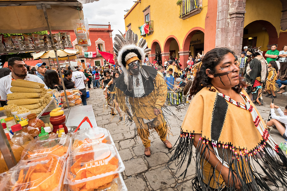 Mexican Concheros dance past a food vendor in the Jardin Allende during the week long fiesta of the patron saint Saint Michael October 1, 2017 in San Miguel de Allende, Mexico.