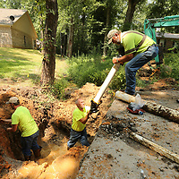 Seth Johnson, from left, preps the existing water line as Mike Jackson gets the new line from Timmy Hood as water crews in Saltillo redirect a water line in town for a new storm drain.