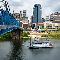 Cincinnati skyline with a riverboat, John Roebling Bridge, and downtown city office buildings including Omnicare building, US Bank building, and Scripps Center building. Photo was taken in July 2012.