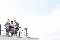 Businesspeople standing at terrace railings against sky