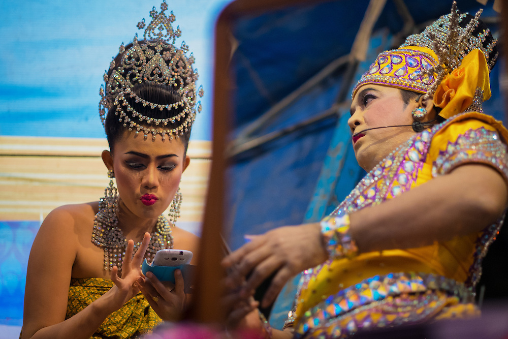 Likay (Thai folk theatre) performers backstage texting and warming up before their performance in Nakhon Nayok, Thailand, March 19, 2015.