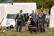 A member of the 124th New York State Volunteers, at right, cleans his weapon in the Union camp during a Civil War reenactment at the Orange County Farmers Museum on Sept. 23, 2006. Other military and civilian reenactors dressed in period uniforms and clothing are also in the camp.
