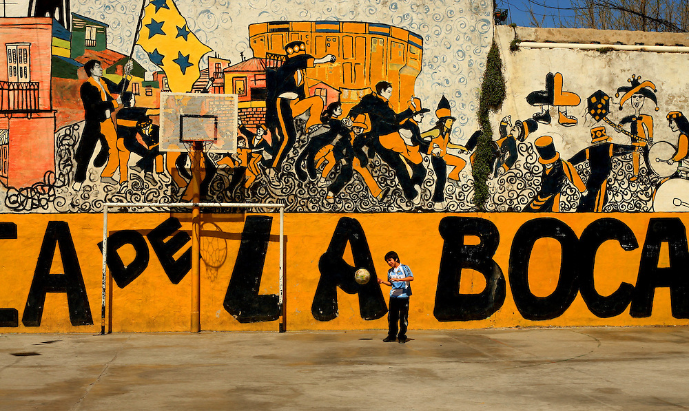 a youngboy plays football infront of a mural depicting the area of Buenos Aires known as Boca, home of Argentinian football club, Boca Juniors , the club Maradona played for.
