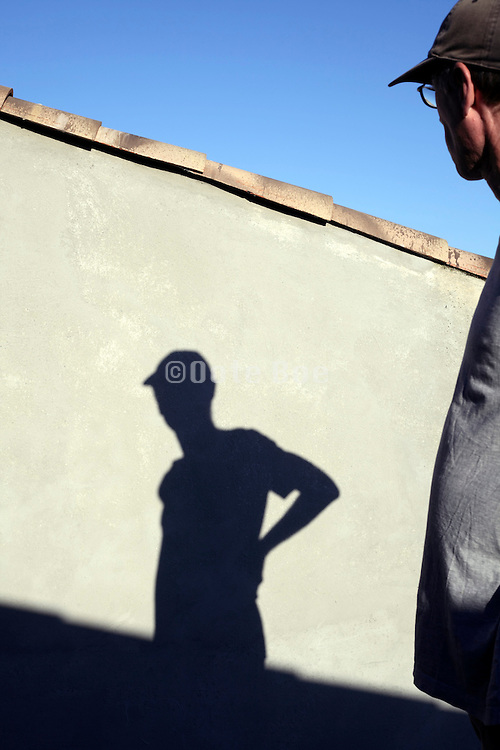 male person looking at its own shadow