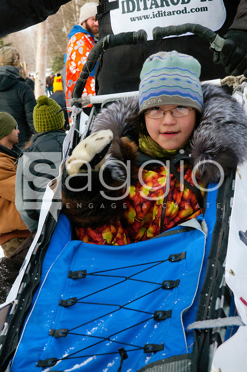 Musher John Baker's Iditarider waves as she passes through a crowd along the Chester Creek Trail during the 2011 Iditarod Ceremonial Start.
