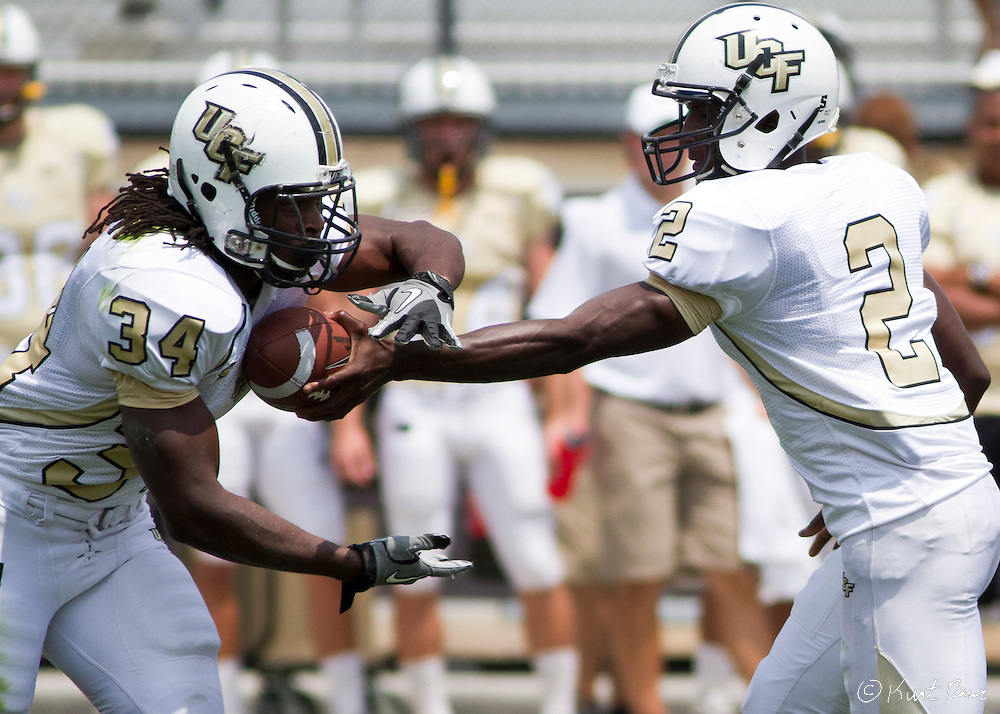UCF quarterback Jeffrey Godfrey (2)gives the ball to UCF running back Brynn Harvey (34) during the Spring Football Game at Bright House Stadium, Orlando, FL on April 16, 2011.  ..