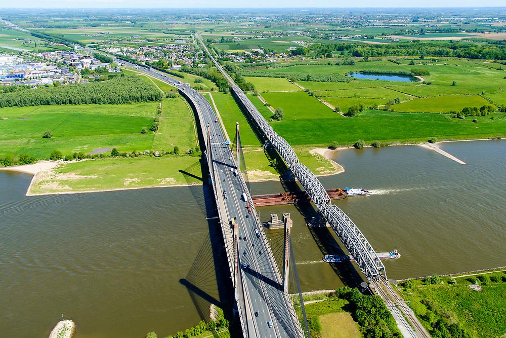 Nederland, Gelderland, Zaltbommel, 13-05-2019; bruggen over de rivier de Waal bij Zaltbommel. Naast de spoorbrug, spoorlijn Utrecht - Den Bosch, de Martinus Nijhofbrug voor autoverkeer op rijksweg A2. Duwbak passsert de bruggen.<br /> Bridges over the River Waal. Railway bridge, railway line Utrecht - Den Bosch and the Martinus Nijhof bridge, motorway A2.<br /> aerial photo (additional fee required); luchtfoto (toeslag op standard tarieven); copyright foto/photo Siebe Swart