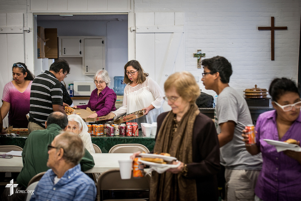 Gloria Palacios is the center of a circle of parishioners eating and chatting together after worship at El Calvario Lutheran Church on Sunday, April 17, 2016, in Brownsville, Texas. LCMS Communications/Erik M. Lunsford