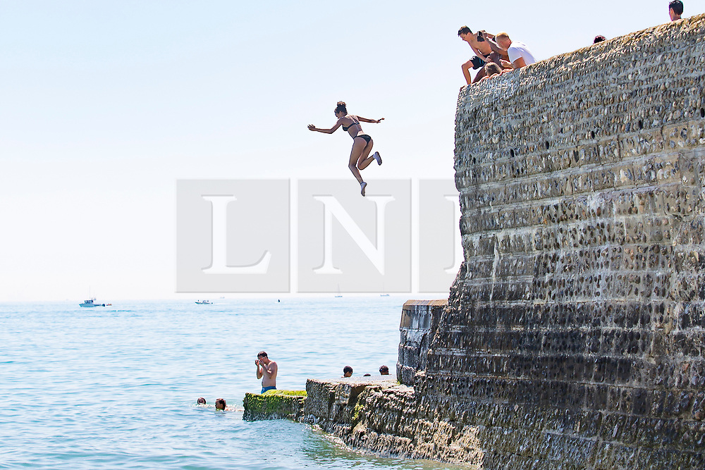 © Licensed to London News Pictures. 09/07/2017. Brighton, UK. A member of the public jumps, also known as tombstoning of the pontoon as visitors take advantage of the sunny weather to relax and sunbath on the beach in Brighton and Hove. Photo credit: Hugo Michiels/LNP