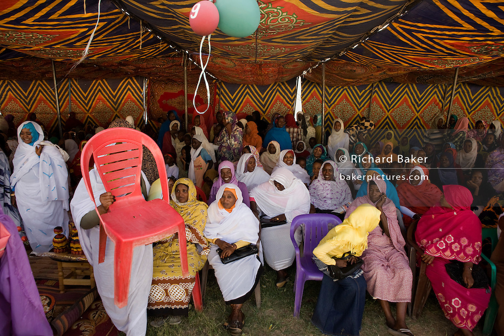 Ladies attending the first-ever international Conference on Womens' Challenge in Darfur, gather to hear speeches and traditional songs under the cool shade of a canopy outside the compound walls belonging to the Govenor of North Darfur in Al Fasher (also spelled, Al-Fashir) where the women from remote parts of Sudan gathered to discuss peace and political issues and celebrate Darfurian culture.