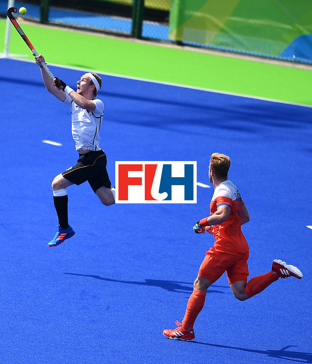 Germany's Christopher Ruhr (L) jumps for the ball beside Netherlands' Mink van der Weerden during the men's Bronze medal field hockey Netherlands vs Germany match of the Rio 2016 Olympics Games at the Olympic Hockey Centre in Rio de Janeiro on August 18, 2016. / AFP / MANAN VATSYAYANA        (Photo credit should read MANAN VATSYAYANA/AFP/Getty Images)