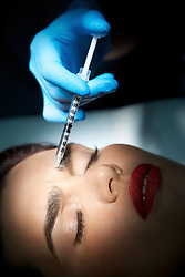 Woman Receiving Botox Injection on Forehead - Close-up view