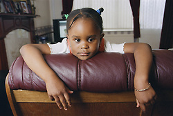 Young girl leaning over the back of a sofa staring; looking thoughtful,