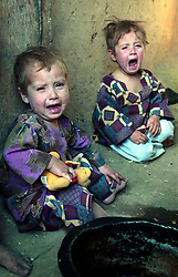 KABUL,AFGHANISTAN - SEPT. 12:  Fatima and Nadia, both orphans living at the Shahad Nik Mohammed orphanage  in Kabul, Afghanistan cry September 12,2002. The children only had tea to drink this morning because there was not even money for bread which costs about five cents a loaf. They are living in desperate conditions as this country struggles to rebuild itself.   (Photo by Ami Vitale/Getty Images)