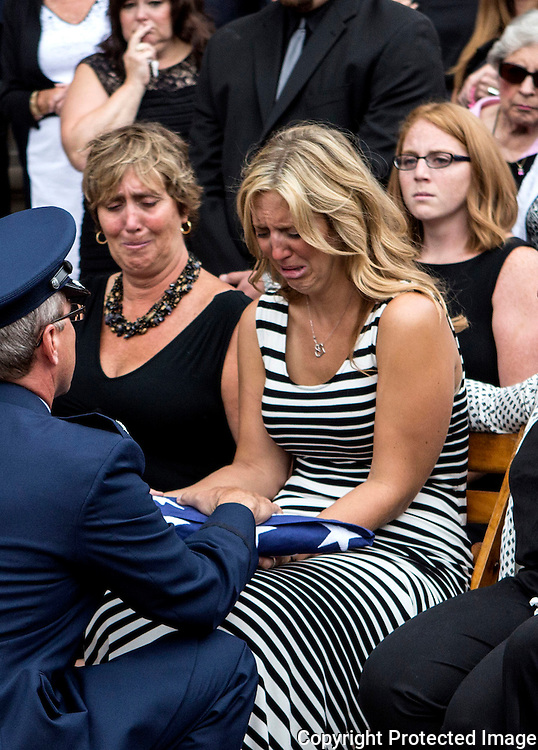 Alyssa Richeson, surrounded by family and friends, is presented a flag at the funeral of her husband. Captain Nathan Richeson received full military honors at Swasey Chapel Tuesday afternoon.  Richeson, who grew up in Granville, served as a pilot in the Air National Guard. He was tragically killed changing a tire on the side of the road by a distracted driver. The couple were celebrating their two-year wedding anniversary.