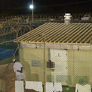 """A detainee looks out from the fence surrounding his cell in Camp 4 at the detention facility in Guantanamo Bay, Cuba. Camp 4 is a communal style camp where more compliant detainees live in small groups and have access to a more open air environment. Approximately 250 """"unlawful enemy combatants"""" captured since the September 11, attacks on the United States continue to be held at the detention facility.(Image reviewed by military official prior to transmission)."""