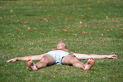 © Licensed to London News Pictures. 22/08/2015. London, UK. A man sunbathes in Green Park. Photo credit: Pete Maclaine/LNP