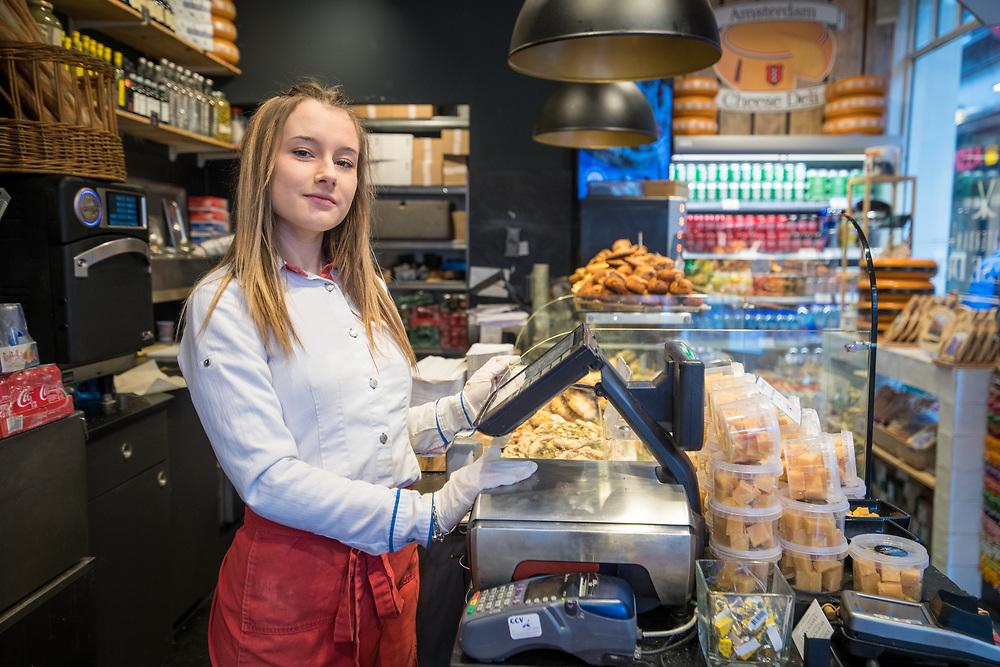 Young female cashier at cheese deli in Amsterdam Netherlands.
