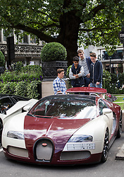 © Licensed to London News Pictures. 27/07/2015. London, UK. Children admire a Bugatti Veyron outside the Dorchester Hotel in London. Kensington and Chelsea Borough Council have announced plans that will make it a criminal offence to cause excessive noise unnecessarily, which will aim to stop showboating by drivers revving their engines, or super-fast accelerating. Photo credit : James Gourley/LNP