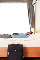 Side view of young businessman sleeping in bed by luggage at hotel room