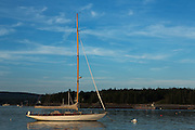 Southwest Harbor, ME - 12 August 2014. Sloop Isla on a mooring in the late afternoon off Clark Point, Greening Island in the background.