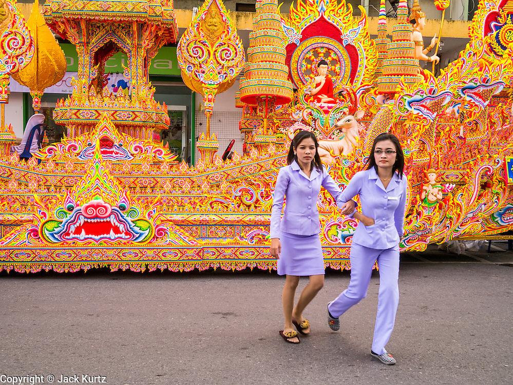 02 NOVEMBER 2012 - HAT YAI, SONGKHLA, THAILAND: Thai office workers walk past an Ok Phansa carriage in Hat Yai, Songkhla, Thailand. Hat Yai is the commercial center of south Thailand and a popular weekend vacation destination for Malaysian and Singaporean tourists.    PHOTO BY JACK KURTZ