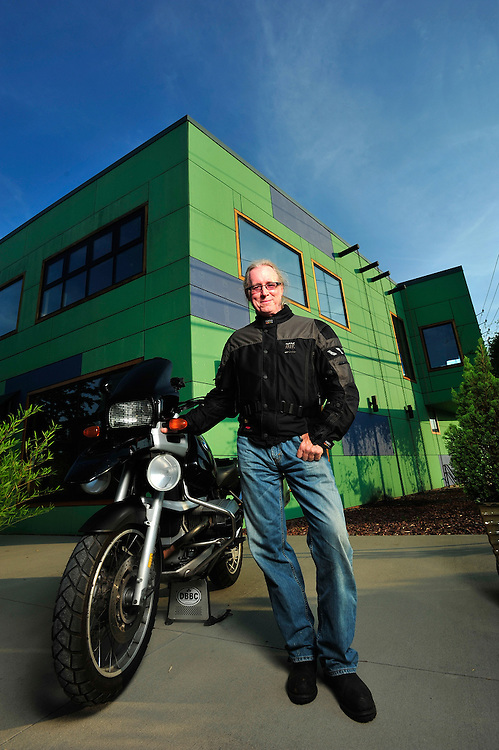 Mike Kilpatrick poses in front of his building with the motorcycle he traveled to Alaska and Central America on Monday, June 28, 2010 in Athens, Ga..