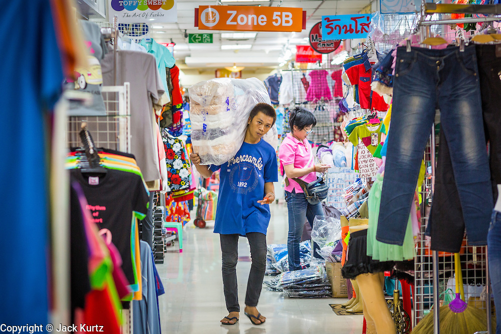 06 JUNE 2013 - BANGKOK, THAILAND:     A vendor carries a load of clothes to his wholesale clothing stand in Bobae Market in Bangkok. Bobae Market is a 30 year old market famous for fashion wholesale and is now very popular with exporters from around the world. Bobae Tower is next to the market and  advertises itself as having 1,300 stalls under one roof and claims to be the largest garment wholesale center in Thailand.       PHOTO BY JACK KURTZ