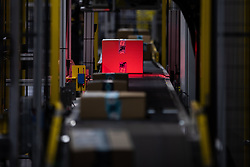 "© Licensed to London News Pictures . 04/12/2019. Manchester , UK . Packaged parcels move along a conveyor belt and are scanned , inside the ""MAN1"" Amazon fulfilment centre warehouse at Manchester Airport in the North West of England . Photo credit : Joel Goodman/LNP"