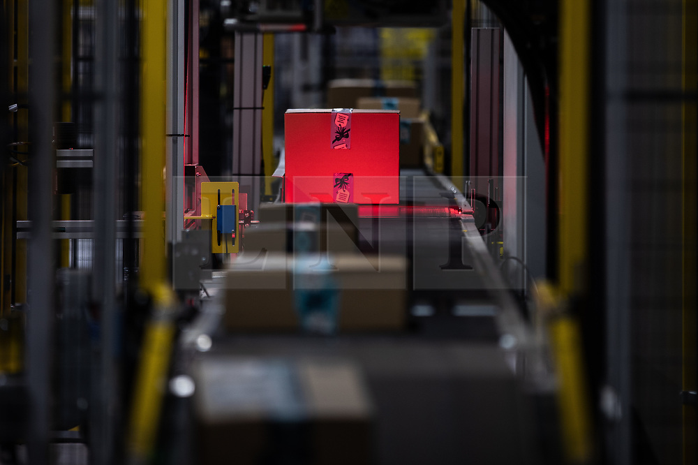 """© Licensed to London News Pictures . 04/12/2019. Manchester , UK . Packaged parcels move along a conveyor belt and are scanned , inside the """"MAN1"""" Amazon fulfilment centre warehouse at Manchester Airport in the North West of England . Photo credit : Joel Goodman/LNP"""