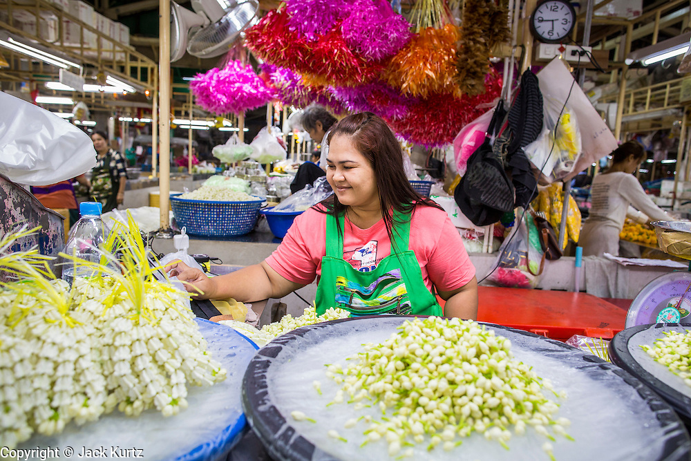 09 OCTOBER 2012 - BANGKOK, THAILAND:  A vendor makes flower garlands in the Bangkok Flower Market. The Bangkok Flower Market (Pak Klong Talad) is the biggest wholesale and retail fresh flower market in Bangkok. It is also one of the largest fresh fruit and produce markets in the city. The market is located in the old part of the city, south of Wat Po (Temple of the Reclining Buddha) and the Grand Palace.    PHOTO BY JACK KURTZ
