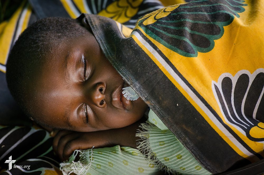 A very sick young girl waits for transport to the hospital during the Mercy Medical Team clinic Thursday, June 12, 2014, at the Luanda Doho Primary School in Kakmega County, Kenya. LCMS Communications/Erik M. Lunsford