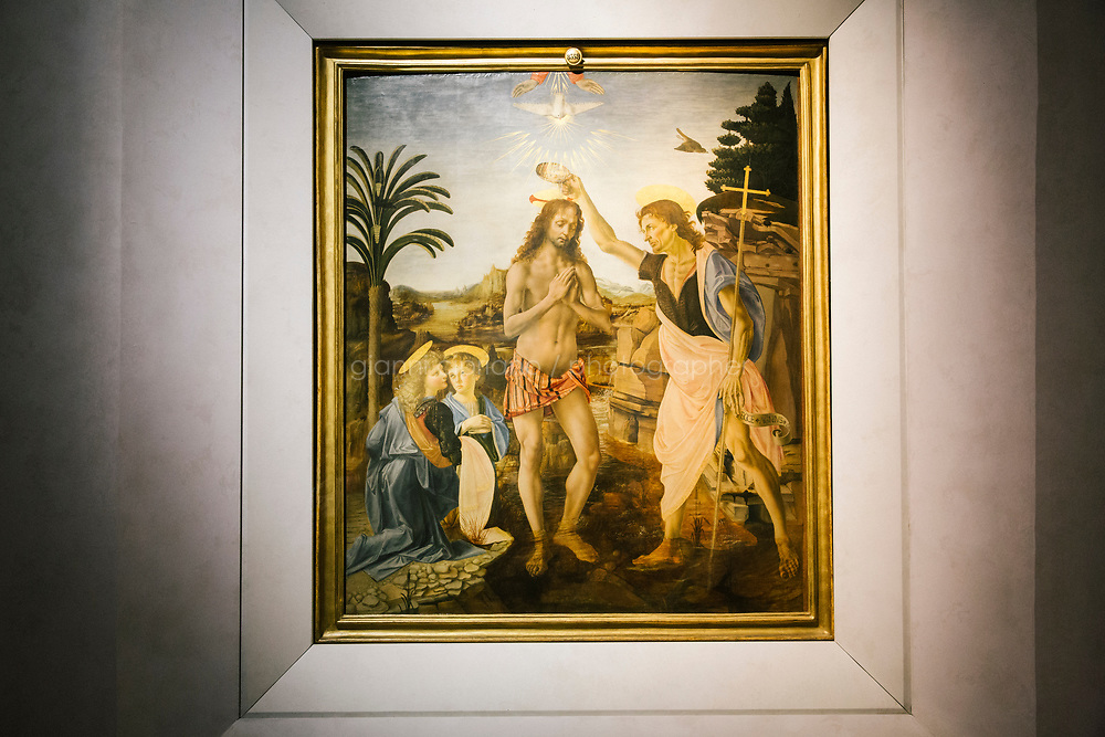 FLORENCE, ITALY - 3 JUNE 2018: &quot;The Baptism of Christ&quot; (1472-1475 ca) by Leonardo da Vinci, is seen here at the Uffizi, before being relocated next month to a new room, in Florence, Italy, on June 3rd 2018.<br /> <br /> As of Monday June 4th 2018, Room 41 or the &ldquo;Raphael and Michelangelo room&rdquo; of the Uffizi is part of the rearrangement of the museum's collection that has<br /> been defining Uffizi Director Eike Schmidt&rsquo;s grander vision for the Florentine museum.<br /> Next month, the museum&rsquo;s Leonardo three paintings will be installed in a<br /> nearby room. Together, these artists capture &ldquo;a magic moment in the<br /> first decade of the 16th century when Florence was the cultural and<br /> artistic center of the world,&rdquo; Mr. Schmidt said. Room 41 hosts, among other paintings, the dual portraits of Agnolo Doni and his wife Maddalena Strozzi painted by Raphael round 1504-1505, and the &ldquo;Holy Family&rdquo;, that Michelangelo painted for the Doni couple a year later, known as the<br /> Doni Tondo.