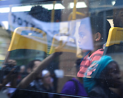 A young child looks out a bus window at protestors as they march past holding signs, chanting and blocking traffic. Protestors rally in reaction to the announcement of homicide charges towards police officers in connection with the April 12th death of Freddie Gray on May 2, 2015, in Baltimore, Md. (Photo By / Chris Post)