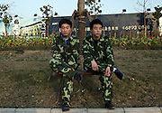 Two security guards in matching camouflage uniforms keep watch near a building site in the Pudong new city area of Zhuopou in Shanghai.