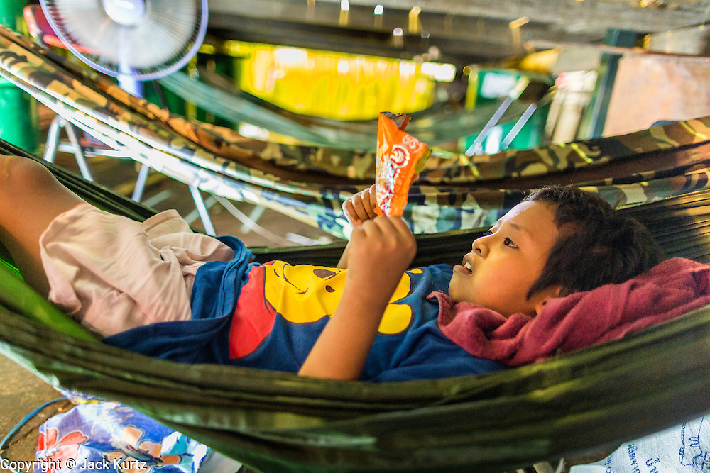 27 APRIL 2013 - BANGKOK, THAILAND:  The child of an opera performer relaxes in a hammock beneath the stage during a Chinese opera show in the Talat Noi neighborhood of Bangkok's Chinatown. Chinese opera was once very popular in Thailand and is usually performed in the Teochew language. Millions of Chinese emigrated to Thailand (then Siam) in the 18th and 19th centuries and brought their cultural practices with them. Recently its popularity has faded as people turn to performances of opera on DVD or movies. There are as many 30 Chinese opera troupes left in Bangkok. They travel from Chinese temple to Chinese temple performing on stages they put up in streets near the temple, sometimes sleeping on hammocks they sling under their stage. The opera troupes are paid by the temple, usually $700 to $1000 a night.   PHOTO BY JACK KURTZ