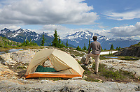 Adult male admiring view from  backcountry campsite. Yellow Aster Butte Basin, Mount Baker Wilderness. Mount Shuksan is in the distance. North Cascades Washington